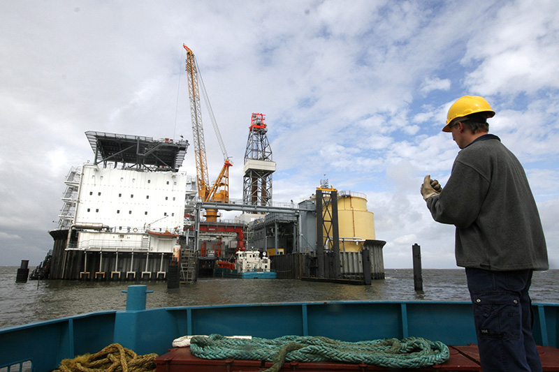 A worker prepares to dock with a support ship at the artificial Mittelplate drilling and production island for oil in the Wattenmeer tidelands off the coast of the German state of Schleswig-Holstein noth-west of Cuxhaven