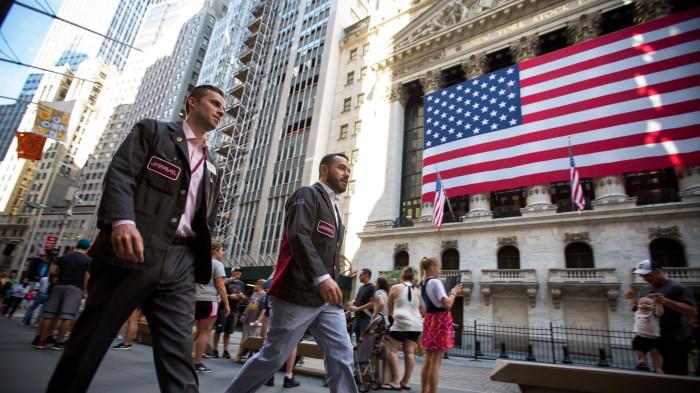 Трейдеры на фоне здания Нью-Йоркской фондовой биржи