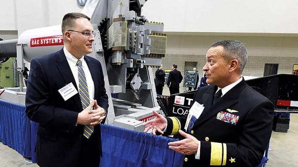 Ведущий инженер Центра надводной войны ВМС США Бен Макглассон (слева) на выставке S&T EXPO обсуждает с контр-адмиралом Мэтом Винтером плюсы и минусы рельсотронов (на заднем плане ствол ЭМП корпорации BAE Systems).