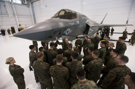 Major Mike Rountree, (C) a marine fighter attack training officer, shows naval flight students a U.S. Marine F-35B Joint Strike Fighter Jet during a roll-out ceremony at Eglin Air Force Base in Florida, February 24, 2012.  The B model of the new single-engine, supersonic fighter jet can take off from shorter runways and can hover and land like a helicopter, according to a military statement. Picture taken February 24, 2012.  REUTERS/Michael Spooneybarger  (UNITED STATES - Tags: MILITARY) - RTR2YFY4
