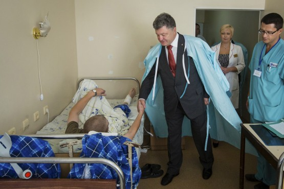Ukrainian President Poroshenko shakes hands with serviceman who was wounded during Monday's protest outside parliament building, at Ukrainian Interior Ministry's hospital in Kiev