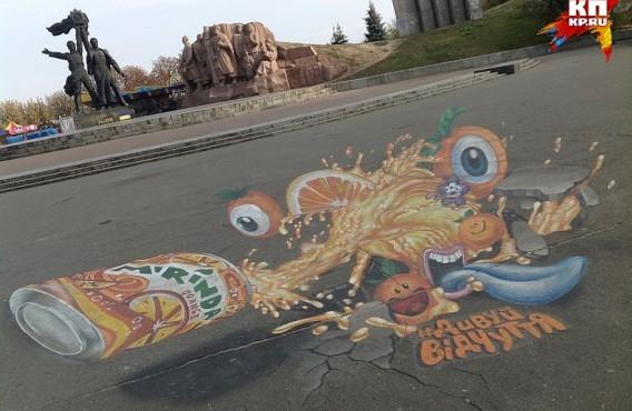 Под памятником дружбы народов появилось гигантское рекламное граффити газировки. Жуткий апельсиновый монстр тянет синий язык к оранжевой банке