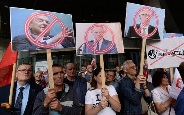 Плакаты с портретами финансиста Джорджа Сороса, президента Европейского совета Дональда Туска и первого вице-президента Европейской комиссии Франса Тиммерманса во время акции протеста в Варшаве