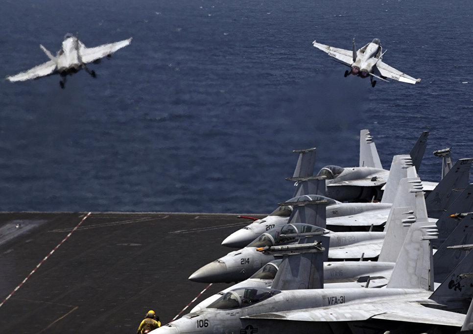 Истребители США F / A-18 вылетают с летной палубы авианосца США USS George H.W. Bush в Персидском заливе